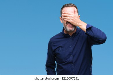 Middle age hoary senior man over isolated background smiling and laughing with hand on face covering eyes for surprise. Blind concept.