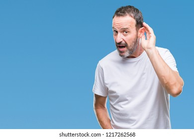 Middle age hoary senior man wearing white t-shirt over isolated background smiling with hand over ear listening an hearing to rumor or gossip. Deafness concept.