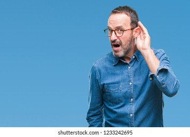 Middle age hoary senior man wearing glasses over isolated background smiling with hand over ear listening an hearing to rumor or gossip. Deafness concept.