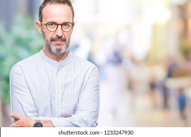 Middle age hoary senior man wearing glasses over isolated background with serious expression on face. Simple and natural looking at the camera.