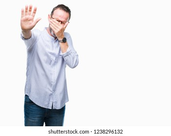 Middle age hoary senior man wearing glasses over isolated background covering eyes with hands and doing stop gesture with sad and fear expression. Embarrassed and negative concept.