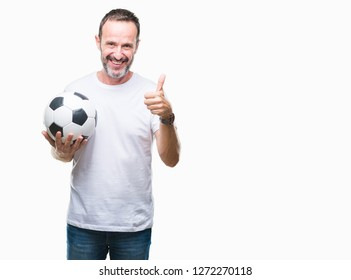 Middle age hoary senior man holding soccer football ball over isolated background happy with big smile doing ok sign, thumb up with fingers, excellent sign
