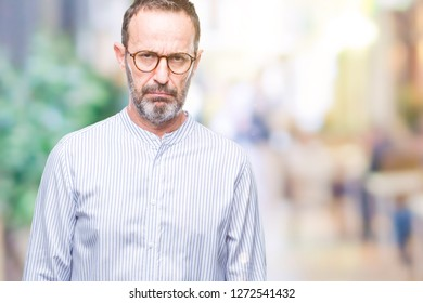 Middle age hoary senior man wearing glasses over isolated background skeptic and nervous, frowning upset because of problem. Negative person.