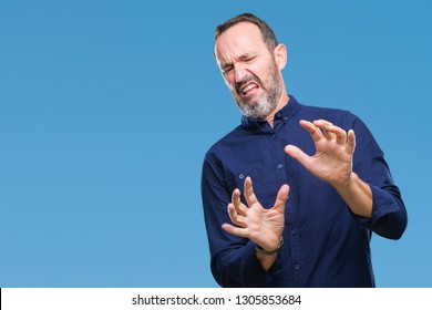 Middle age hoary senior man over isolated background disgusted expression, displeased and fearful doing disgust face because aversion reaction. With hands raised. Annoying concept.