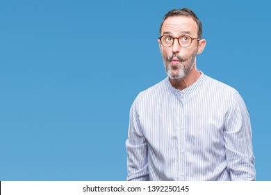 Middle age hoary senior man wearing glasses over isolated background making fish face with lips, crazy and comical gesture. Funny expression.