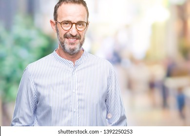 Middle age hoary senior man wearing glasses over isolated background with a happy and cool smile on face. Lucky person.
