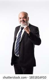 Middle age Indian asian businessman with beard wearing elegant black suit and pointing with hand and finger. presenting product, service or copy space