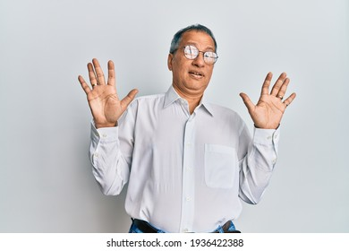 Middle age indian man wearing casual clothes and glasses afraid and terrified with fear expression stop gesture with hands, shouting in shock. panic concept.