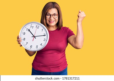 Middle age latin woman holding big clock screaming proud, celebrating victory and success very excited with raised arms