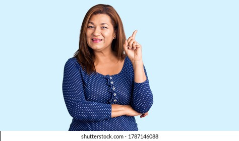 Middle age latin woman wearing casual clothes smiling happy pointing with hand and finger to the side
