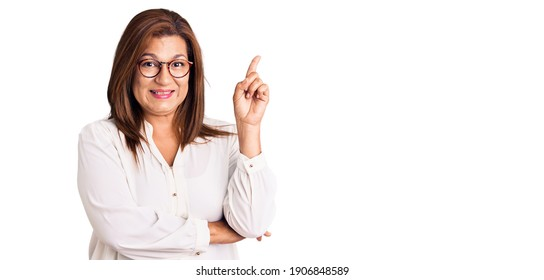 Middle age latin woman wearing casual clothes and glasses with a big smile on face, pointing with hand and finger to the side looking at the camera.