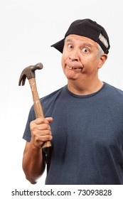 Middle age man with bad teeth wearing a baseball cap holding a hammer with a funny expression.