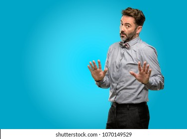 Middle age man, with beard and bow tie annoyed with bad attitude making stop sign with hand, saying no, expressing security, defense or restriction, maybe pushing