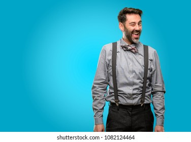 Middle age man, with beard and bow tie blinking eyes with happy gesture