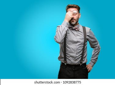 Middle age man, with beard and bow tie with sleepy expression, being overworked and tired, rubbes nose because of weariness