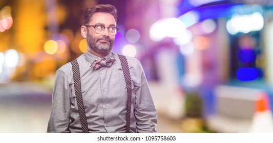 Middle age man, with beard and bow tie making funny face fooling at night club