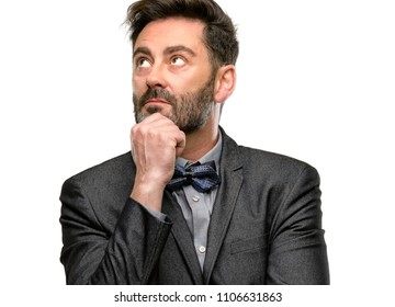 Middle age man, with beard and bow tie thinking and looking up expressing doubt and wonder isolated over white background