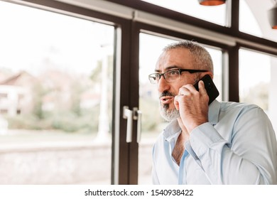 Middle age man in blue shirt talking on the phone next to the office window. Business concept