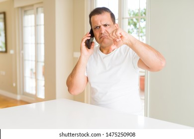 Middle age man calling using smartphone with angry face, negative sign showing dislike with thumbs down, rejection concept