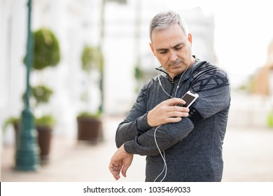 Middle age man choosing a playlist for exercising in the city on his smartphone on armband