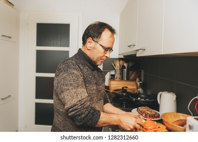 Middle age man cooking dinner in the kitchen, peeling off potato with peeler