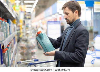 Middle age man customer buying engine lubricating oil in the car supermarket. Difficult decision which motor oil to buy