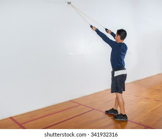 Middle age man demonstrates lat pulldown strength exercise at start position.