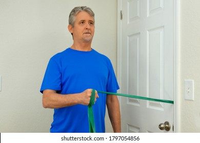 Middle age man doing shoulder surgery physical therapy with resistance rubber band exercises at home to strengthen the deltoid muscles to fully recover normal strength and flexibility.
