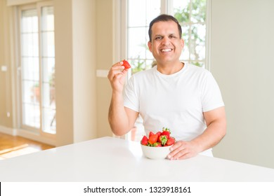 Middle age man eating strawberries at home with a happy face standing and smiling with a confident smile showing teeth