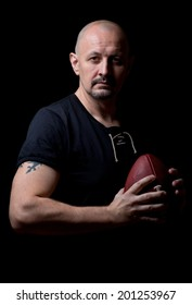 middle age man with football portrait on dark background