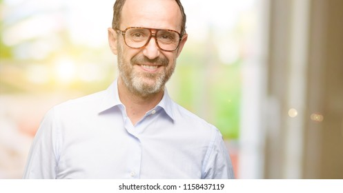 Middle age man with glasses confident and happy with a big natural smile laughing