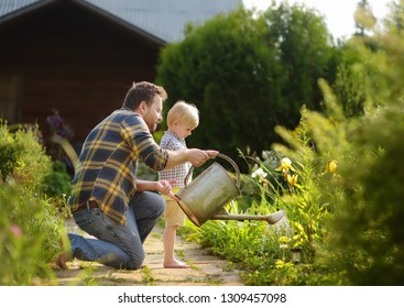 Der mittelalterliche Mann und sein kleiner Sohn, der Blumen im Garten bei sonniger Sommerzeit gießt. Gartenarbeit mit kleinen Kindern und Familien