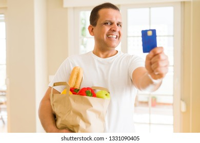 Middle age man holding groceries bag and showing credit card
