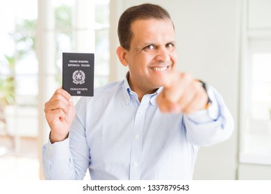 Middle age man holding holding passport of Italy pointing with finger to the camera and to you, hand sign, positive and confident gesture from the front