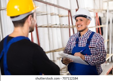 Middle age man offering contract to employee at workshop