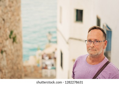 Middle age man on summer vacation by the sea, wearing glasses