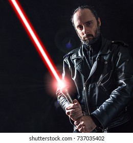 Middle age man posing on black background with a leather jacket and a laser sword