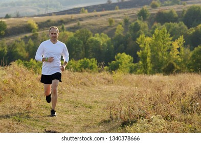 Middle age man running alone outdoors countryside at fall
