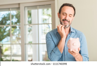 Middle age man save money on piggy bank serious face thinking about question, very confused idea