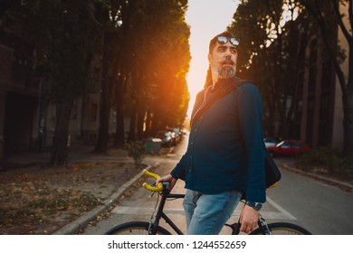 Middle age man sightseeing the city with his bike beside him