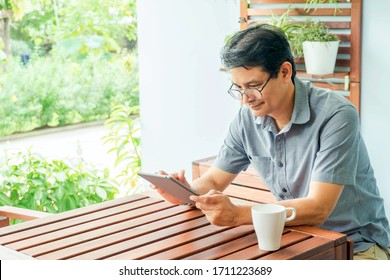 Middle age  man sitting in the house and using   tablet for online working at home for self quarantine. Corona virus outbreak situation. Self quarantine at home prevention COVID-19.