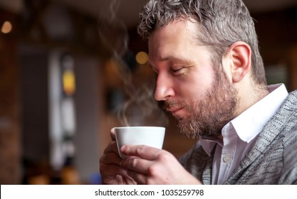 Middle age man smelling aroma of coffee in the cafe