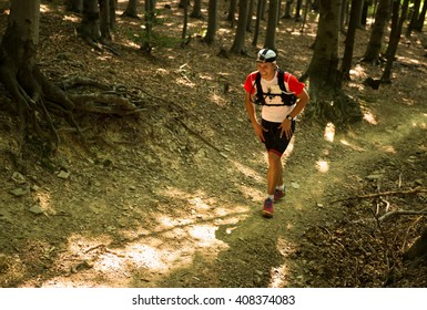 middle age man in sportswear running ultra race up the hill on a dry forest trail in hot summer