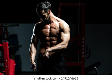 Middle Age Man Standing Strong In The Gym And Flexing Muscles - Muscular Athletic Bodybuilder Fitness Model Posing After Exercises