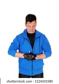 A middle age man standing waist up in a blue jacket putting on his