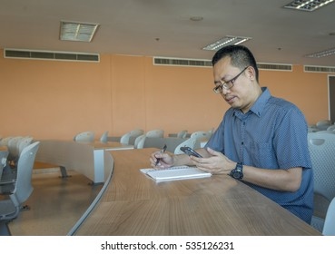 Middle age man is studying alone in classroom