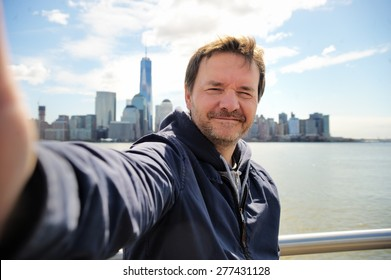 Middle age man taking a self portrait (selfie) with Manhattan skyscrapers in New York City