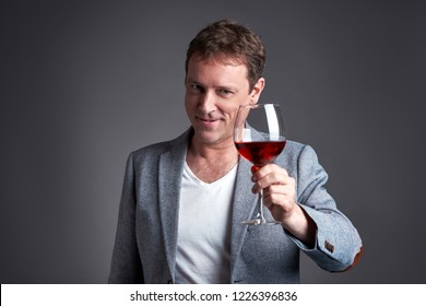 A middle age man toasting with a glass of wine