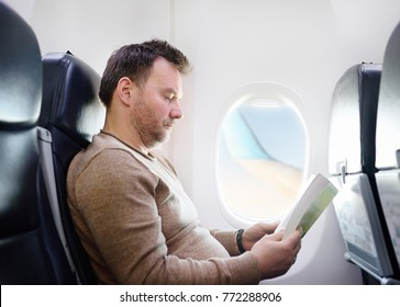 Middle age man traveling by an airplane. Person sitting by aircraft window and reading a book during the flight. Transportation concept