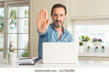 Middle age man using laptop at home with open hand doing stop sign with serious and confident expression, defense gesture